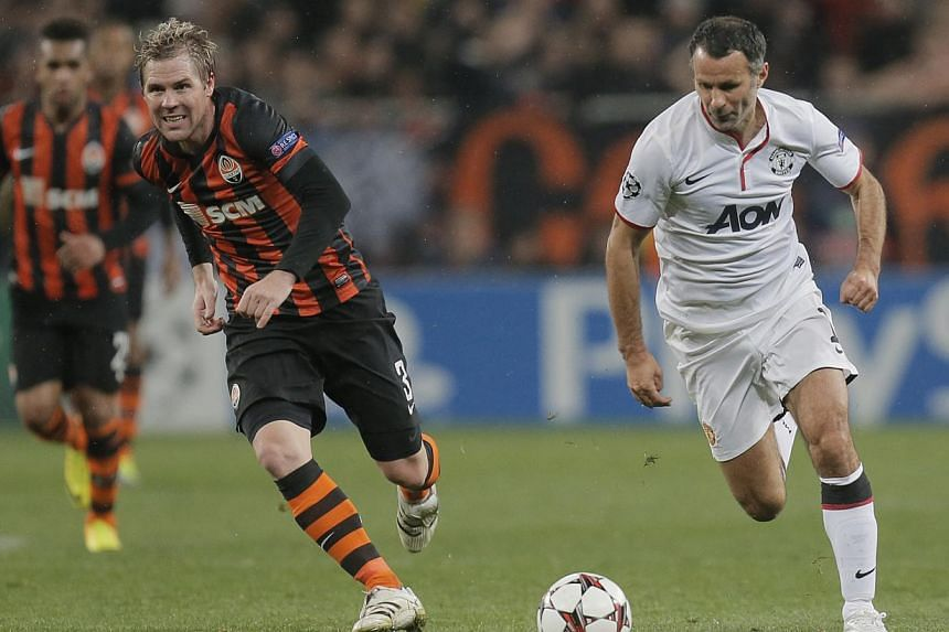 Manchester United's Ryan Giggs(right) and Shaktar Donetsk's Tomas Hubschman battle for the ball during their Champions League Group A soccer match at Donbass Arena Stadium in Donetsk, Ukraine, on Wednesday, Oct. 2, 2013. Manchester United veteran Rya