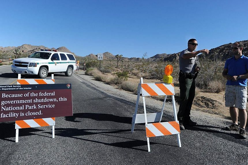 A US park ranger gives a visitor suggestions of other nearby places he can visit while Joshua Tree National Park was shut down, at the entrance to Joshua Tree, California, on Oct 2, 2013.  Thousands have been left angry at being locked out of la