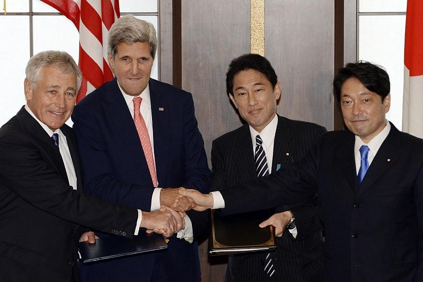 (From Left) US Secretary of Defence Chuck Hagel, US Secretary of State John Kerry, Japan's Foreign Minister Fumio Kishida and Japan's Defence Minister Itsunori Onodera shake hands after exchanging documents after their security talks a