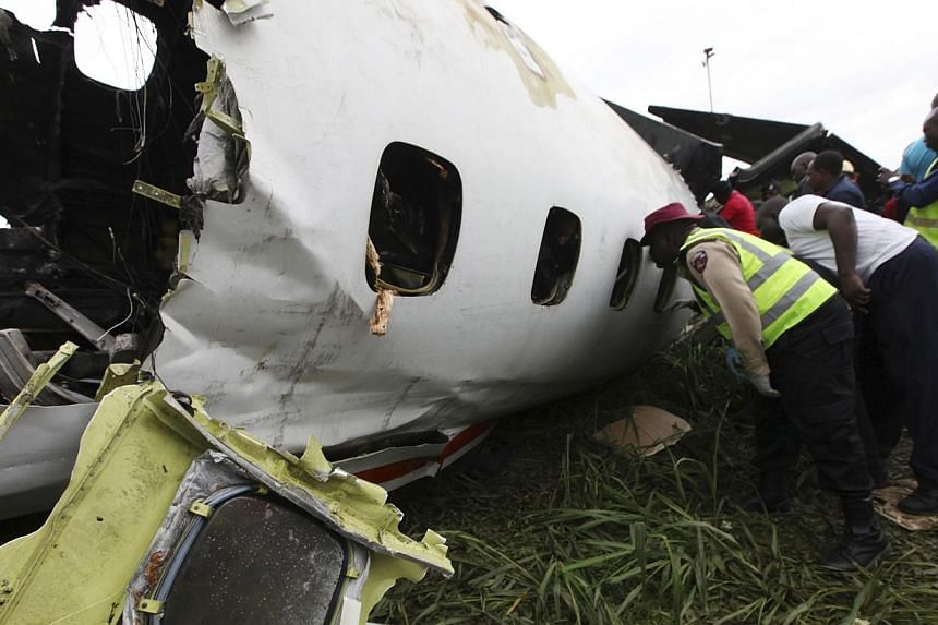 Rescue workers peer into thewreckage of an Associated Airlines plane that crash-landed at Sahara Airport shortly after take-off at Lagos airport on Oct 3, 2013. -- PHOTO: AP