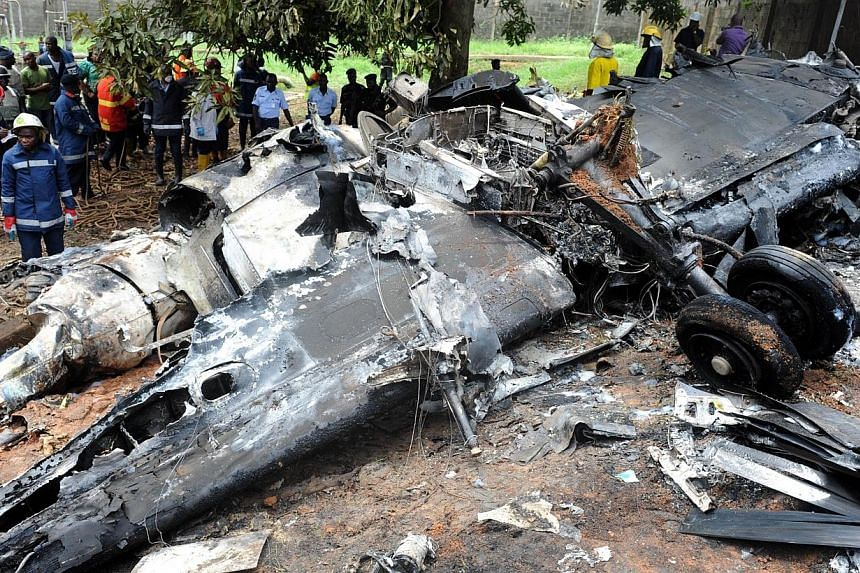 Rescue workers gather aroundthewreckage of an Associated Airlines plane that crash-landed at Sahara Airport shortly after take-off at Lagos airport on Oct 3, 2013. -- PHOTO: AFP