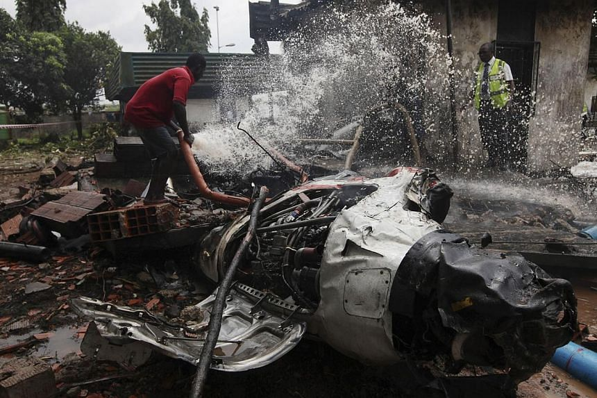 A rescue worker douses a part of the wreckageof an Associated Airlines plane that crash-landed at Sahara Airport shortly after take-off at Lagos airport on Oct 3, 2013. -- PHOTO: AP