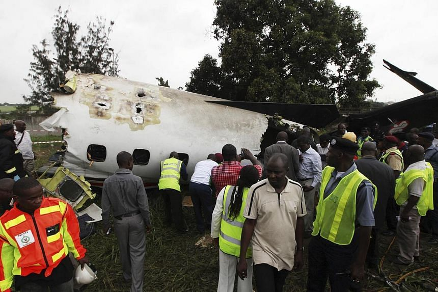 Rescue workers gather around the wreckage of an Associated Airlines plane that crash-landed at Sahara Airport shortly after take-off at Lagos airport on Oct 3, 2013. -- PHOTO: AP