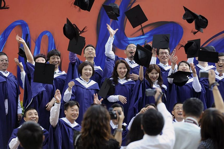 MBA graduates from NUS posing for pictures at their commencement ceremony. NUS rose three spots to 26th this year and held on to its second position in Asia, after Tokyo University.
