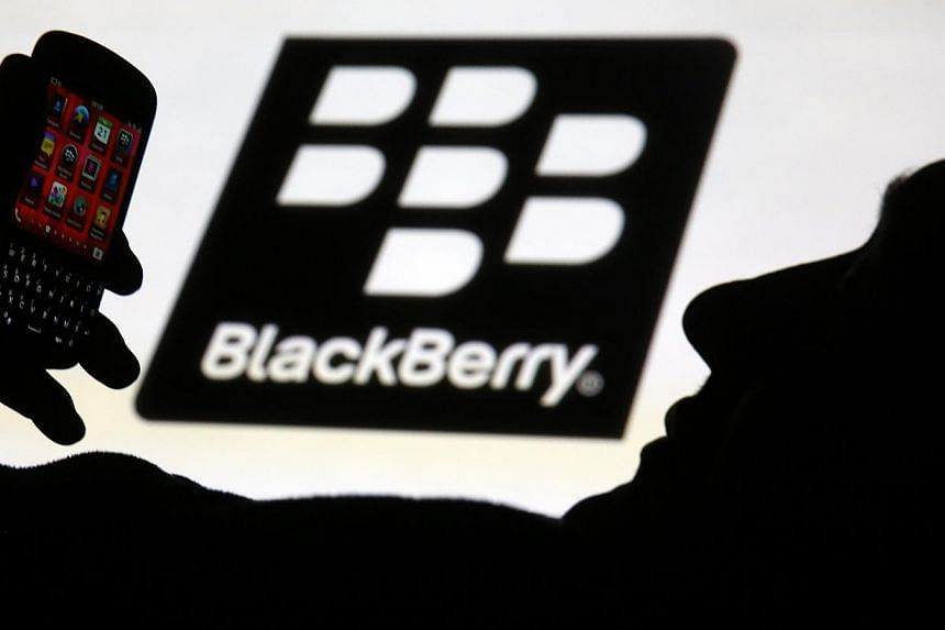 A man is silhouetted against a video screen with the Blackberry logo as he poses with a Blackberry Q10. The private equity firm Cerberus Capital Management is interested in a bid for troubled Canadian smartphone maker BlackBerry, a source familiar wi