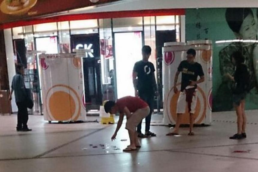 """The alleged attacker in the Lot 1 stabbing incident on Tuesday, only known as """"Yang"""", is seen in the foreground wearing a red t-shirt. He is seen bent over a pool of blood.The victim, Mr Tan Zhi Long, is seen standing calmly in the background o"""