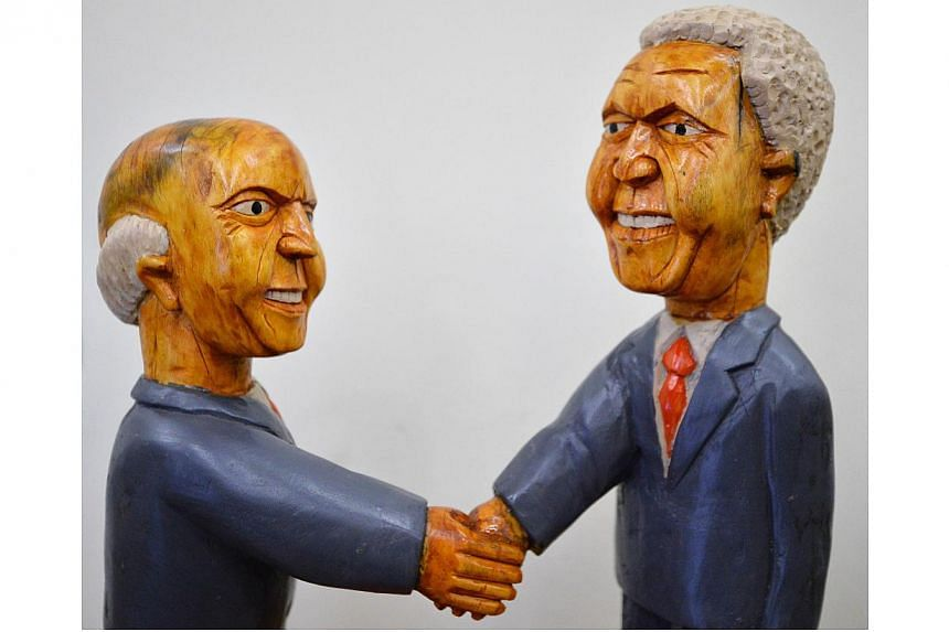 """An art work entitled """"Mandela and De Klerk Shaking Hands'"""" by South African artist Richard Chauke is displayed at the """"We love Mandela"""" exhibition at the South Africa House in central London on Oct 2, 2013. -- PHOTO: AFP"""