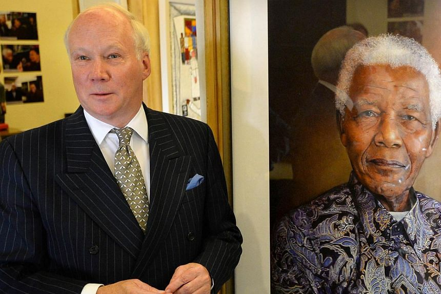 """British artist Richard Stone poses with a print of his portrait of Nelson Mandela painted in 2008 and diplayed at the """"We love Mandela"""" exhibition at the South Africa House in central London on Oct 2, 2013. A portrait of Nelson Mandela by British art"""