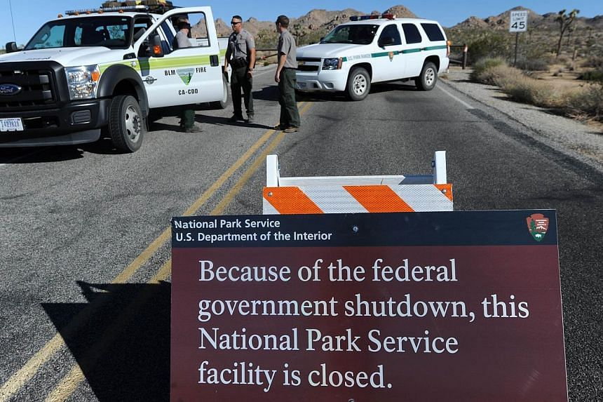 US Park Rangers stand at the closed gate to Joshua Tree National Park, in Joshua Tree, California on Oct 2, 2013, the second day of the US government shutdown. Hundreds of tourists staying in landmark US national parks like Yosemite and the Grand Can
