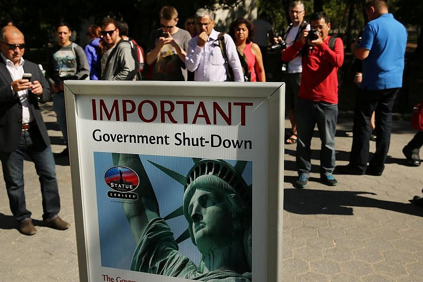 People look at a sign informing them that the Statue of Liberty is closed due to the government shutdown in Battery Park on Oct 1, 2013 in New York City. Federal museums and parks across the nation are closed starting today due to a government shutdo