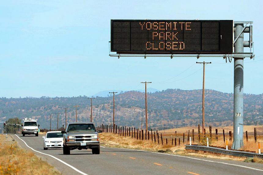 This Tuesday, Oct 1, 2013, photo shows a sign alerting motorists of the closure of Yosemite National Park, California, due to the government shutdown as US park ranger Heidi Schlichting directs visitors. President Barack Obama brought top lawmakers t