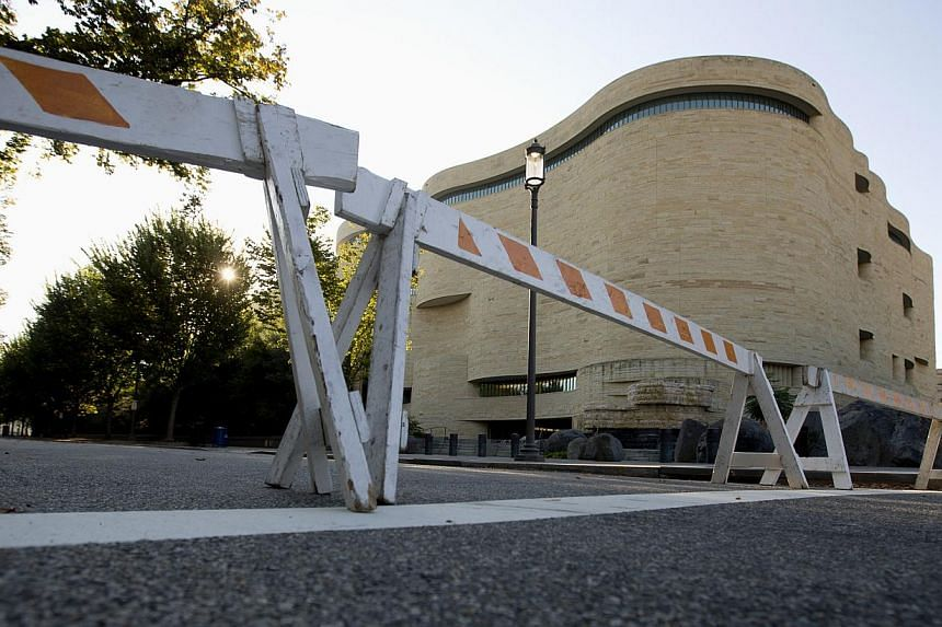 Barricades are posted in front of the closed Smithsonian National Museum of the American Indian in Washington, Wednesday, Oct 2, 2013. The political stare-down on Capitol Hill shows no signs of easing, leaving federal government functions from