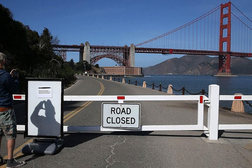 A visitor takes a picture of a sign announcing the closure of the Fort Point National Historic Site due to the partial government shutdown on Oct 1, 2013 in San Francisco, California. Federal museums and parks across the nation are closed starting to