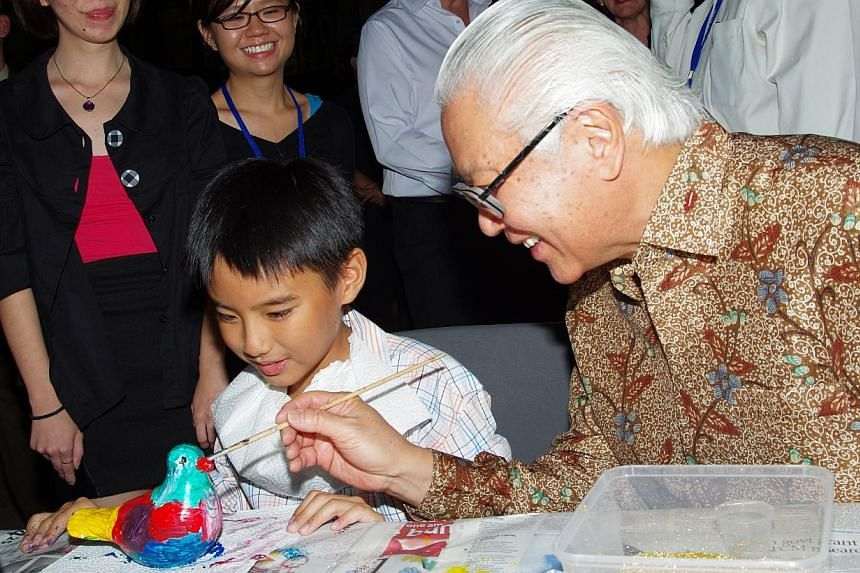 President Tony Tan Keng Yam (right) lends 10-year-old Ethan Wu a helping hand in designing his dove. -- PHOTO: DOVER PARK HOSPICE