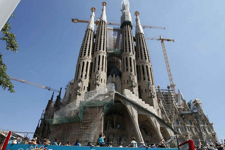 People queue up at a city tour bus stop in front of the Basilica Sagrada Familia in Barcelona on Sept 13, 2013. A 3-D video has been released by the Sagrada Familia Foundation, the body responsible for overseeing the building project, which show