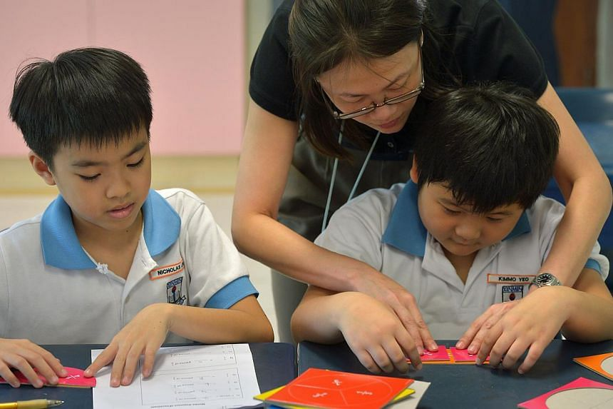 A teacher helping Primary 3 pupils of Xinmin Primary School. Singapore came in 7th out of 21 countries in the 2013 Global Teacher Status Index, with an index ranking of 46.3 out of 100. -- ST FILE PHOTO : KUA CHEE SIONG