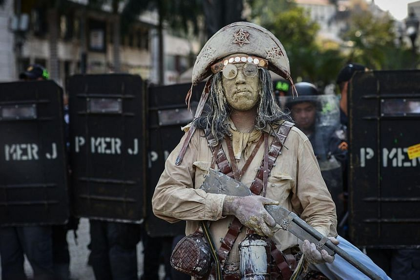 A street performer is seen during a teacher protest against corruption in the office of Rio Governor Sergio Cabral, in Rio de Janeiro, Brazil on Oct 1, 2013. See more pictures from around the world in Through The Lens' Today in Pictures. -- PHOTO: AF