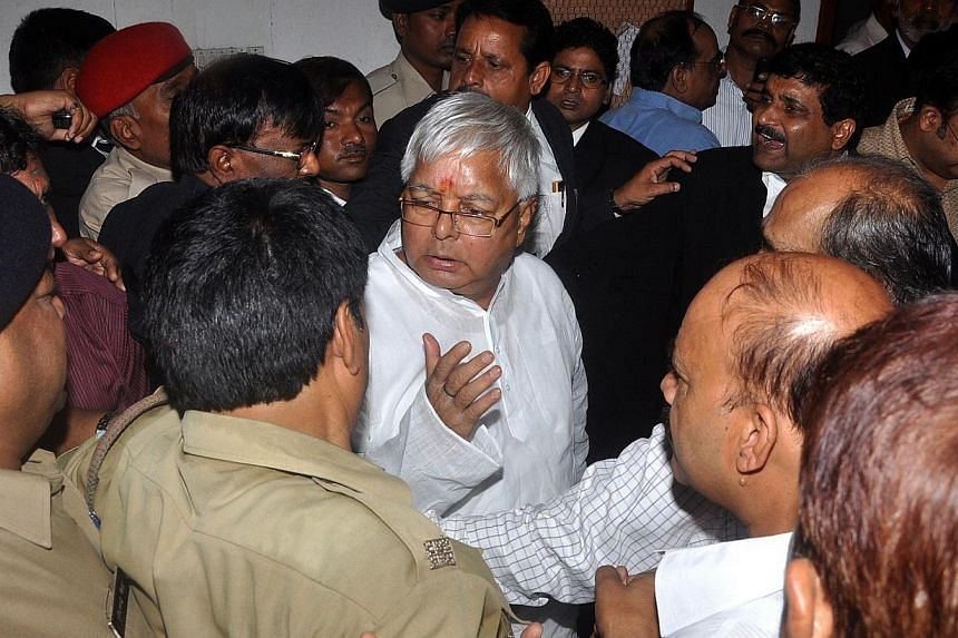Lalu Prasad Yadav, a former Indian federal minister, whose Rashtriya Janata Dal party supports the ruling coalition, is escorted out of court after a hearing in Ranchi, Jharkhand on September 30, 2013. -- PHOTO: AFP