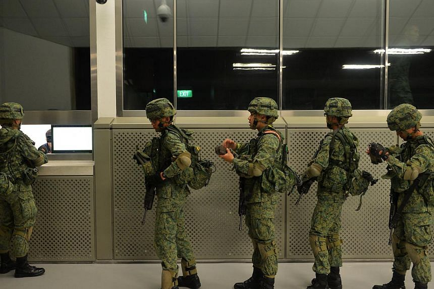 NSmen queuing to return their empty magazines after a firing exercise at a 100m range. Singapore's soldiers will now spend a lot more time sharpening their marksmanship at the Republic's latest indoor firing range that went fully-operational on Frida