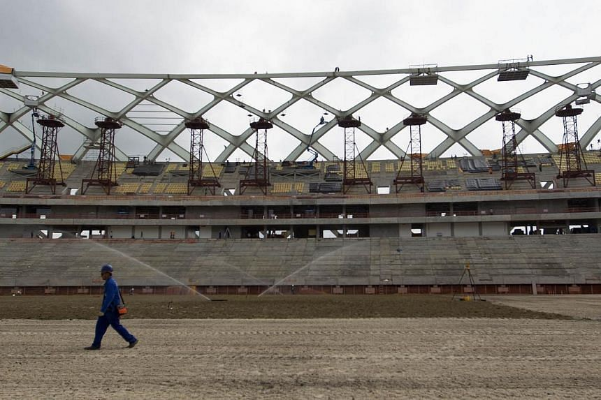 Workers plant grass inside the Arena da Amazonas Stadium in the heart of Brazil's Amazon rainforest in Manaus, on Oct 3, 2013. The stadium will host several 2014 World Cup soccer matches. More than 4.5 million tickets have already been requested for