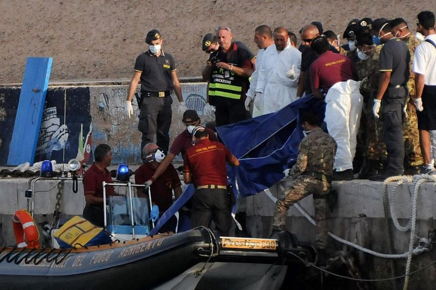 Rescuers lift a body bag as they reach the port of Lampedusa, southern Italy, on Oct 3, 2013. More than 300 people drowned or were feared dead after a boat packed with African migrants caught fire and sank off the southern Italian island of Lamp