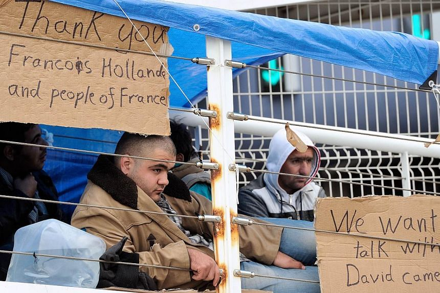 Syrian refugees sit next to placards as they occupy the footbridge of a ferry terminal at Calais port on Oct 4, 2013. France on Friday offered some 60 Syrians the right to seek asylum after the refugees occupied a key point in the Channel port of Cal