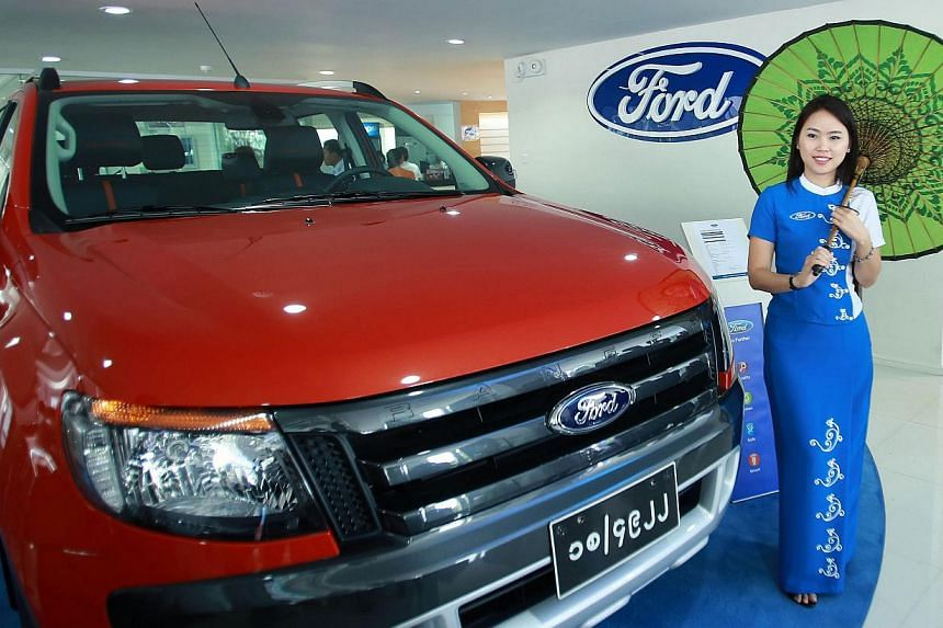 A model poses next to a Ford car at a Ford showroom in Yangon on Oct 4, 2013. Ford Motor Co officially opened its first authorised dealership in Myanmar, joining a rush to set up shop in the former junta-ruled country as the West rolls back sanctions