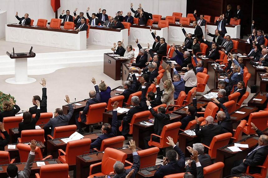 Members of the Turkish parliament vote during a debate to discuss a government proposal to extend by a year a mandate authorising the sending of troops into Syria if needed in Ankara Oct 3, 2013. Syrian President Bashar al-Assad warned Turkey it will