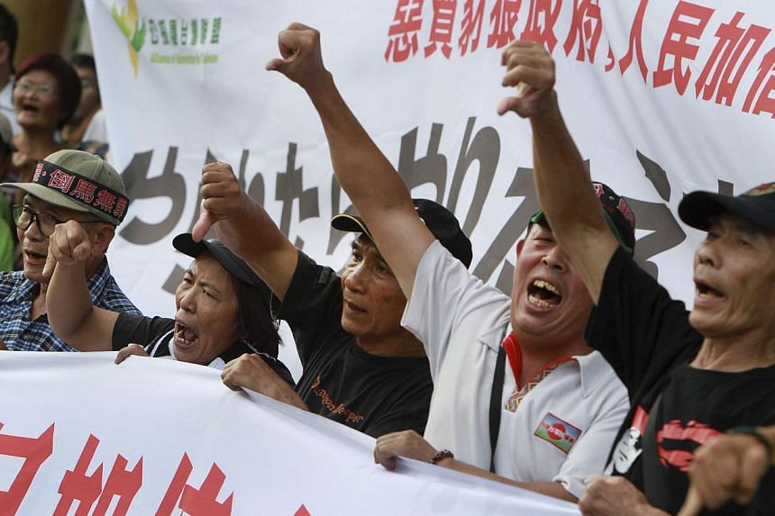 Protesters showing the thumbs-down sign and shouting slogans during a protest against Taiwan President Ma Ying-jeou in Taipei, Taiwan, on Sunday, Sep. 29, 2013. Tens of thousands of Taiwanese were rallying on Sunday against President Ma amid plummeti