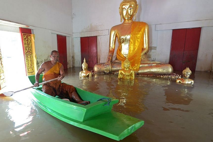 A Buddhist monk paddles a boat past a Buddha statue at a temple in Ayutthaya province, north of Bangkok, on Thursday, Oct 3, 2013. See more pictures from around the world in Through The Lens' Today in Pictures. -- PHOTO: AFP