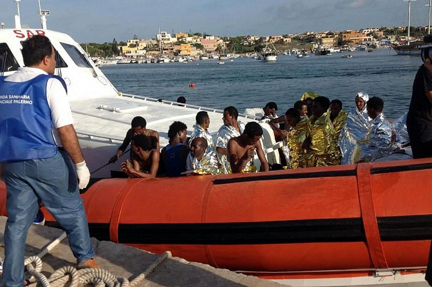 An Italian Coast Guard boat carry rescued migrants as they arrive in the port of Lampedusa on Oct 3, 2013. More than 300 people drowned or were feared dead after a boat packed with African migrants caught fire and sank off the southern Italian island