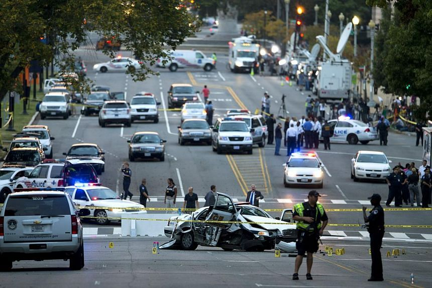 A damaged Capitol Hill police car is surrounded by crime scene tape on Constitution Avenue near the United States Capitol after a car chase and shooting on Oct 3, 2013, in Washington. A dramatic car chase through the streets of Washington from near t