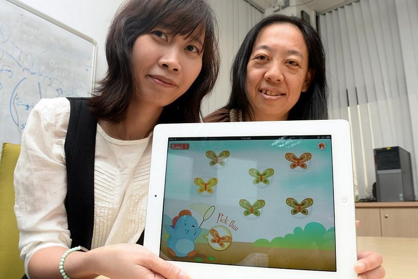 "The game's designer Nguyen Linh Chi (left) and Keio-NUS Cute Centre co-director Ellen Do showcasing the app, which requires pre-school children to ""catch"" butterflies of matching colours by tapping a screen. Those with colour blindness would consiste"