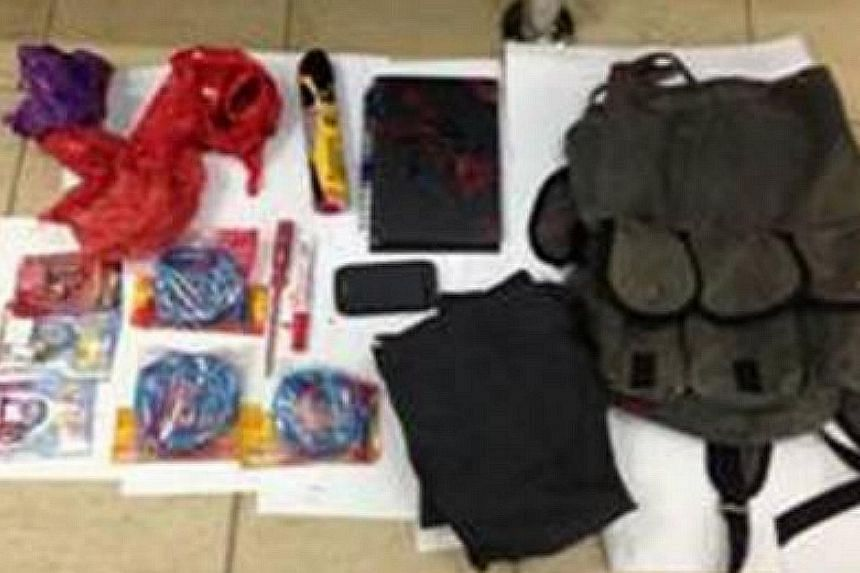 Loanshark-related paraphernalia such as padlocks, paint cans, markers and a mobile phone, were found in the possession of a 31-year-old man who was arrested in connection with a case of loansharking harrassment in Ang Mo Kio housing estate. -- PHOTO: