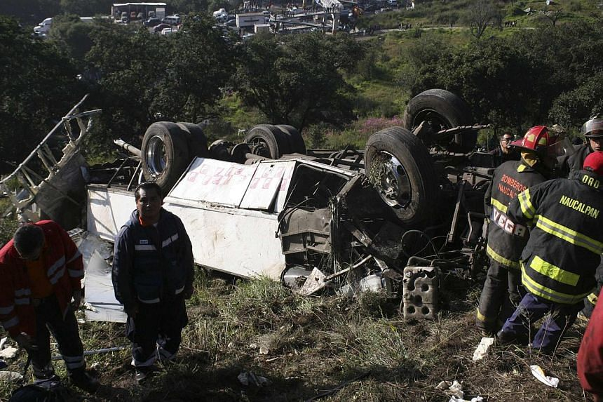 Firefighters and rescue workers stand next to the wreckage of a bus in Naucalpan, on the outskirts of Mexico City, Oct 4, 2013. A bus packed with morning commuters careened off a cliff outside Mexico City on Friday, leaving 14 people dead, inclu