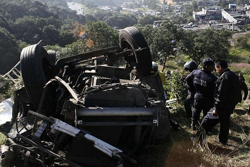 Police officers stand next to the wreckage of a bus in Naucalpan, on the outskirts of Mexico City, on Oct 4, 2013. The bus careened off a cliff, leaving 14 people dead, including a child, and injuring 24 others, officials said. -- PHOTO: REUTERS