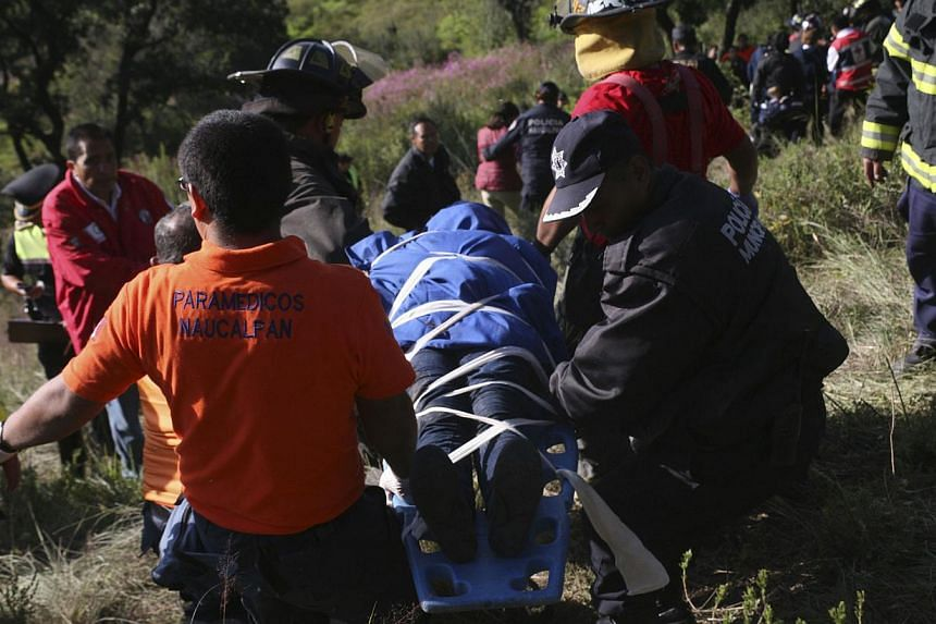 Firefighters and rescue workers carry a body off a ravine from the site of a bus accident in Naucalpan, on the outskirts of Mexico City, on Oct 4, 2013. The bus careened off a cliff, leaving 14 people dead, including a child, and injuring 24 others,