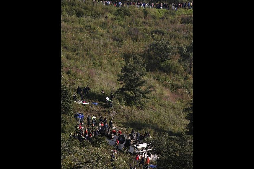 Rescue workers stand at the site of a bus accident in Naucalpan, on the outskirts of Mexico City, on Oct 4, 2013. The bus careened off a cliff, leaving 14 people dead, including a child, and injuring 24 others, officials said. -- PHOTO: REUTERS