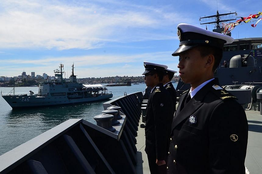 RSN midshipmen lining up on the deck of RSS Endeavour as the Governor-General of Australia Quentin Bryce, accompanied by Britain's Prince Harry, conducts the Ceremonial Fleet Review on board HMAS Leeuwin (left) on Oct 5, 2013.-- PHOTO: MINDEF