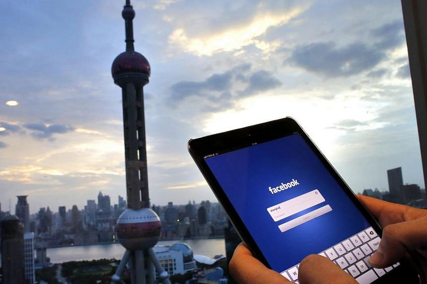 In this photo illustration, a man holds an iPad with a Facebook application in an office building at the Pudong financial district in Shanghai, on September 25, 2013. -- PHOTO: REUTERS
