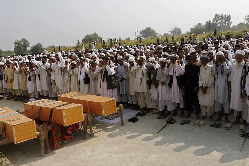 Afghan men praying near the coffins of civilians, who according to the provincial government, were killed in a Nato air strike, on the outskirts of Jalalabad province, on October 5, 2013. At least five civilians were killed overnight in a Nato air st