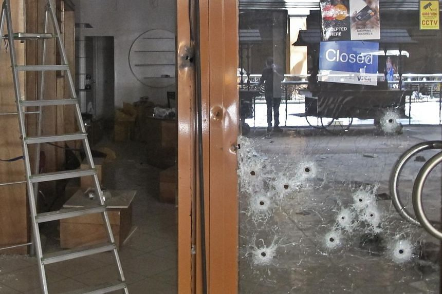 Bullet holes pepper the glass door of a shop in the Westgate Mall in Nairobi, Kenya on Tuesday, Oct 1, 2013. With chilling nonchalance, gunmen who massacred at least 67 people wander through Kenya's Westgate mall, seen for the first time in security