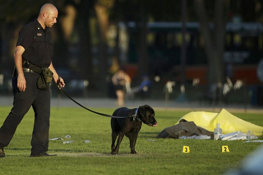 A law enforcement officer uses a police dog to search for evidence at the scene where a man set himself on fire within sight of the US Capitol building on the US National Mall in Washington, Oct 4, 2013. -- PHOTO: REUTERS