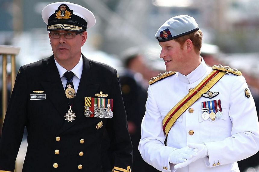 Britain's Prince Harry (right) is met by Vice Admiral Ray Griggs, Chief of Navy before they embark on the HMAS Leeuwin as they attend the 2013 International Fleet Review in Sydney on Oct 5, 2013. -- PHOTO: AFP