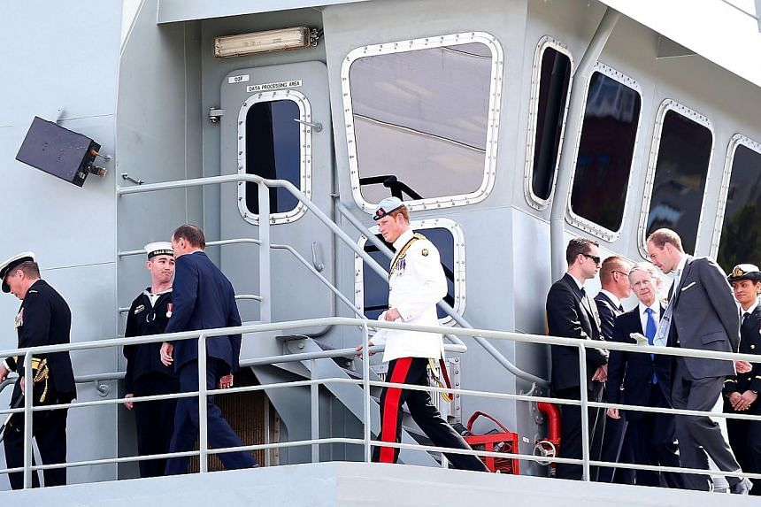 Britain's Prince Harry (centre) embarks on the HMAS Leeuwin as he attends the 2013 International Fleet Review in Sydney on Oct 5, 2013. -- PHOTO: AFP