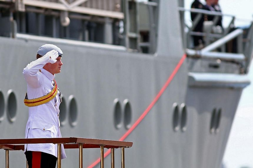 Britain's Prince Harry stands and salutes as he arrives at Garden Island in Sydney to attend the 2013 International Fleet Review on Oct 5, 2013. -- PHOTO: AFP