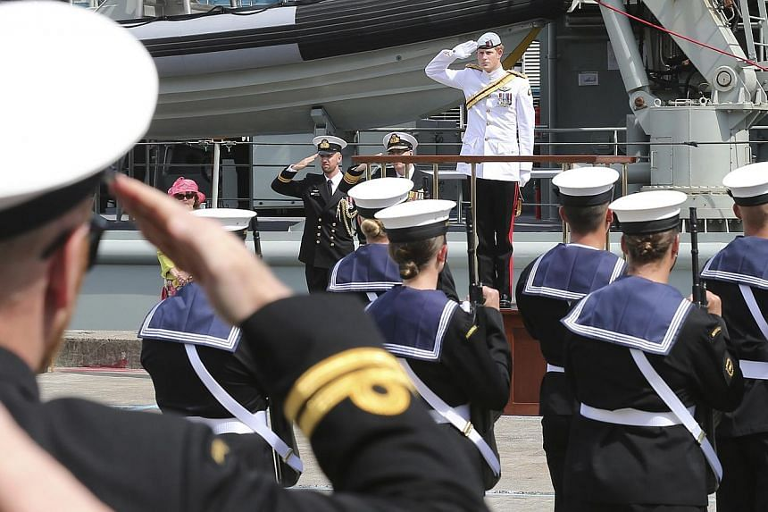 Britain's Prince Harry, center in the background, receives a royal salute from the honor guard at Garden Island Naval base in Sydney, Australia, on Oct 5, 2013 before boarding HMAS Leeuwin to view the International Fleet review. -- PHOTO: AFP
