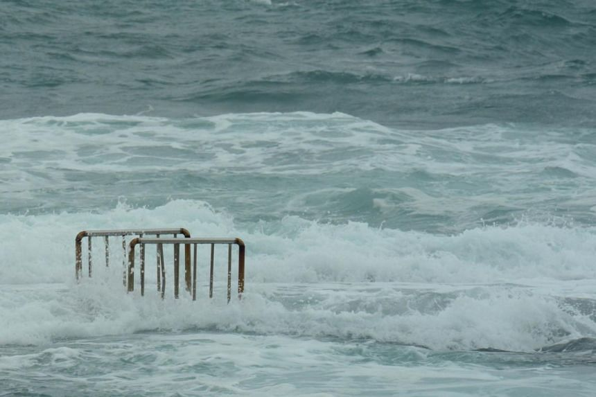 Sea waves cover the ladder bars from a swimming pool at Hoping island, in Keelung, northern Taiwan, as Typhoon Fitow approaches on Oct 5, 2013. Powerful Typhoon Fitow forced flight cancellations and power outages as it barrelled towards Japan's
