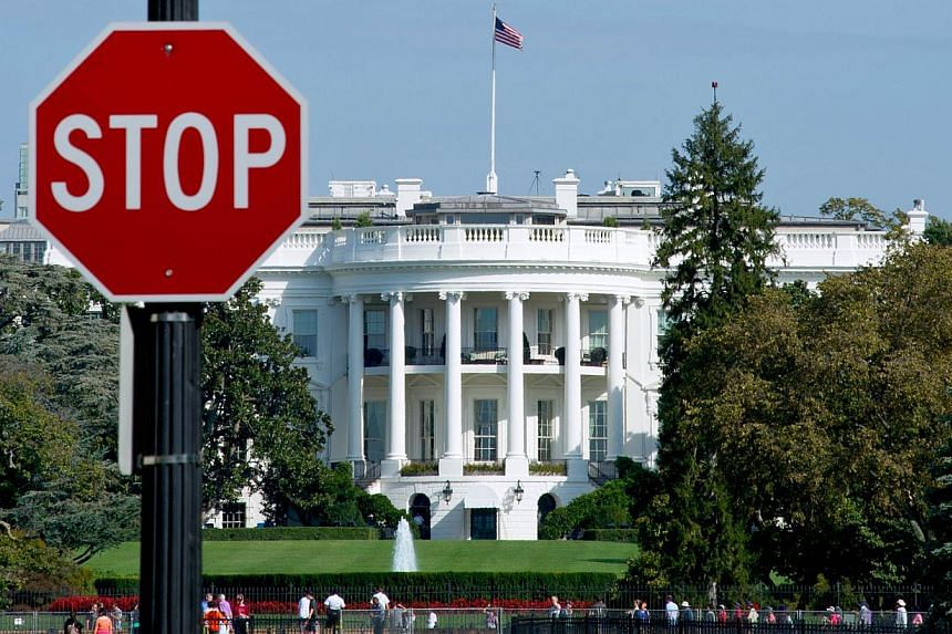 The White House is seen behind a stop sign in Washington, DC, on Oct 1, 2013. The White House warned on Friday that the office which enforces United States sanctions on Iran could not function as most of its staff was furloughed by the government shu