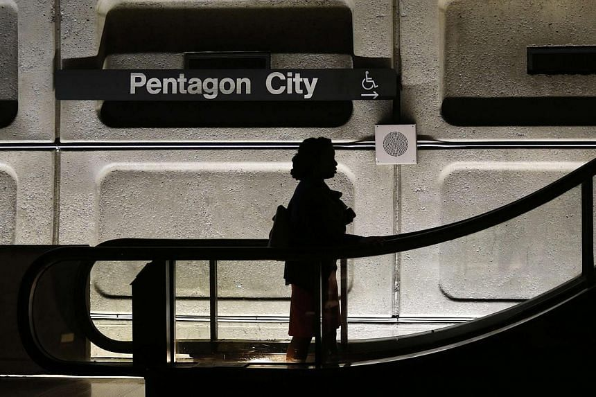 An woman rides an upward escalator at Pentagon City Metro station during rush hour in Washington October 2, 2013. The Pentagon said on Saturday it will recall most of its furloughed employees as a US government shutdown went into its fifth day with n